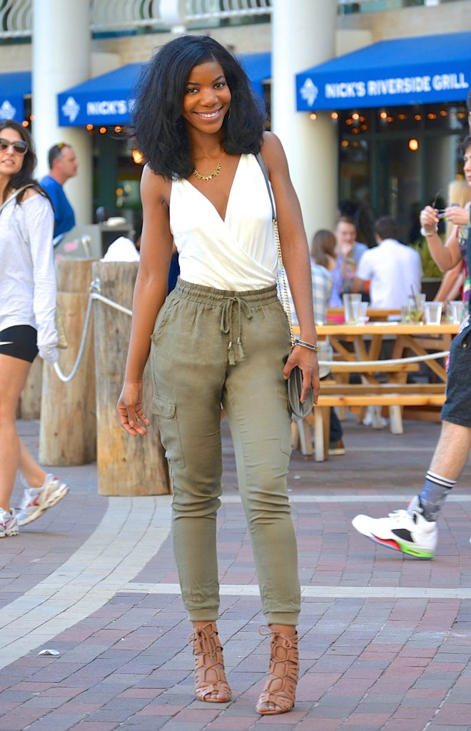 off white low cut fashion nova bodysuit, olive green joggers, tan lace up sandals